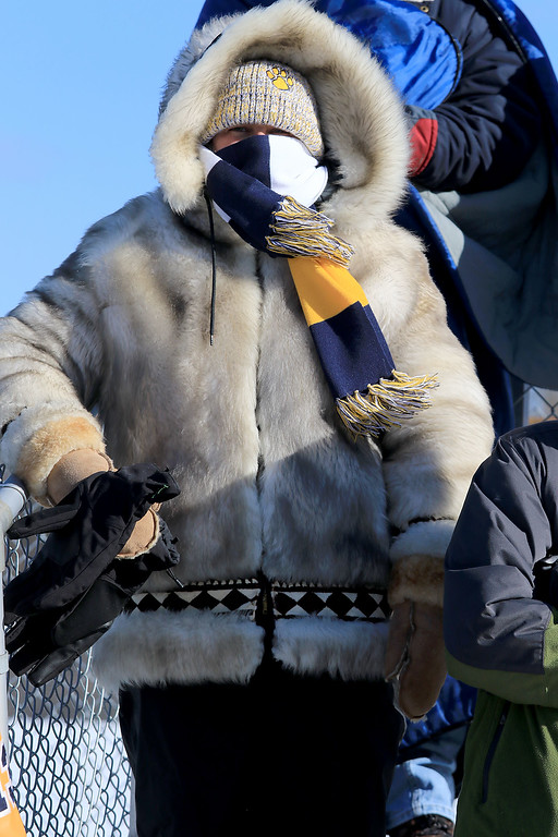 . Littleton High School visited Ayer Shirley Regional High School on Thanksgiving Day for there annual turkey day game. LHS fan Maria Davis stays warm as she cheers on the team and LHS player Brock Davis. SENTINEL & ENTERPRISE/JOHN LOVE