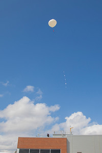 The radiosonde comparison balloon aloft over the UAH SWIRLL building.  The five radiosonde instrument packages can be seen below the balloon as it climbs.