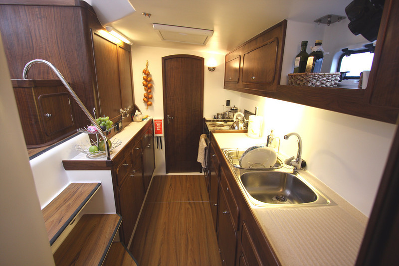 Galley looking forward, sink and stove outboard, abundant counter space and stowage lockers.