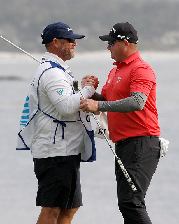. Ted Potter Jr. celebrates with his caddy John Balmer on the 18 green at the Pebble Beach Golf Links after winning 2018 the AT&T Pebble Beach Pro-Am on Sunday, Feb. 11, 2018.  (Vern Fisher - Monterey Herald)