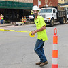 KEVIN HARVISON | Staff photo<br /> Joe Sturgeon, with the city of McAlester Utility Maintenance Department, puts up tape to block a portion of Choctaw Avenue near Second Street Wednesday morning. The construction is the result of an agreement with the city of McAlester and a property owner. The city is tapping into an eight-inch water line under Choctaw Avenue to run a six-inch line up to the front of the building that will be used to connect to a fire suppressant system at The Venue. McAlester City Manager Pete Stasiak said the connection will make it possible for the building owners to connect to the line and install infrastructure for a planned fire suppressant system, which will make it possible for the upper floor to be used. It's the first such fire suppressant line to be placed along Choctaw Avenue with hopes to revitalize the downtown area through utilizing upper floors in many of the buildings.