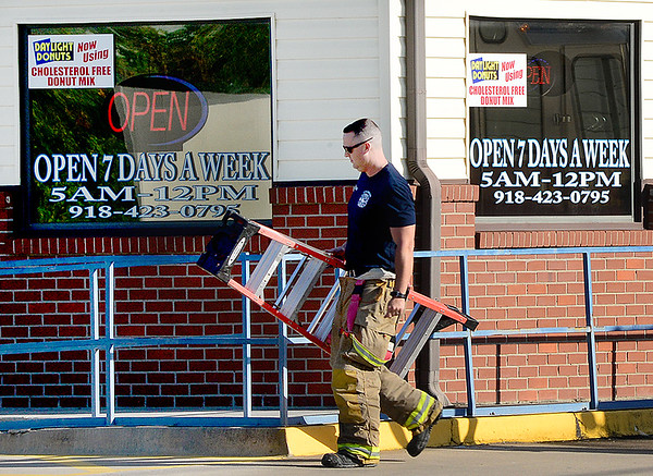 KEVIN HARVISON | Staff photo<br /> A McAlester Fire Fighter prepares to check out the DayLIght Donut shop after a call came into the station Wednesday moring.