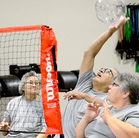 KEVIN HARVISON | Staff photo<br /> Joe Coley, center, of Wilburton, reaches up to return a ball over the net during a chair volleyball game held at the Choctaw Nation of Oklahoma Wellness Center in Crowder.