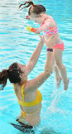 KEVIN HARVISON | Staff photo<br /> Erin Kelley left, lifts Wynnley Long into the air as the two play at Jeff Lee Pool.