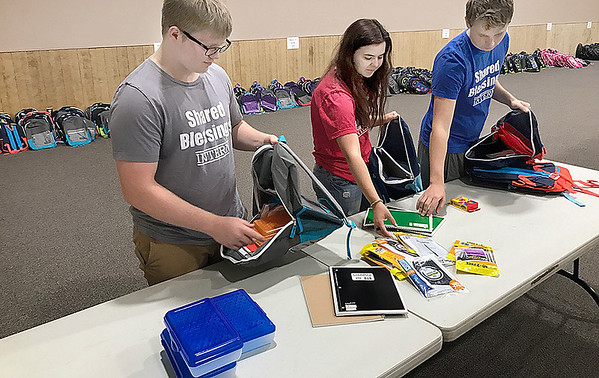 KEVIN HARVISON | Staff photo<br /> Back Packs line the walls as Shared Blessing Interns stuff back packs with school supplies. Pictured from left, Gaevin Jones, Ashley Lovell and Evan Adams.
