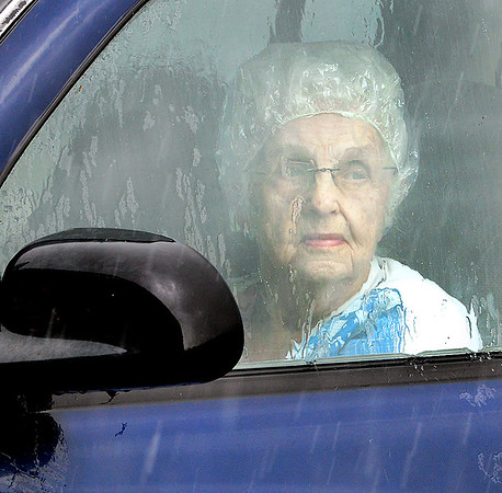 KEVIN HARVISON | Staff photo<br /> An unidentified woman sits in here vehicle Tuesday afternoon waiting for a break in the rain  before exiting.
