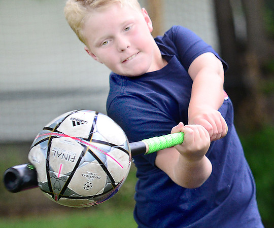 KEVIN HARVISON | Staff photo<br /> Landon Eddy improvizes as he hits a soccer ball with a baseball while playing outside recently.
