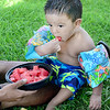 KEVIN HARVISON | Staff photo<br /> Felix Rios takes time from the water to eat some melon.
