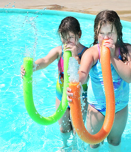 "KEVIN HARVISON | Staff photo Pictured from left, Hope Wilbur and Ambree Parker play the ""water horns"" while spending some time at the Chadick Park wadding pool."
