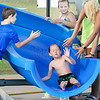 KEVIN HARVISON | Staff photo<br /> A Jeff Lee Pool patron gets high fives as he goes down the pool water slide.