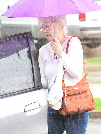 KEVIN HARVISON | Staff photo<br /> An unidentified woman uses an umbrella to shield the rain as gets into her vehicle Tuesday.