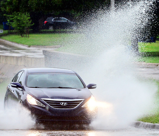 Kevin Harvison | Staff photo<br /> A car passes through standing water Electric Avenue Monday after storms hit the area.