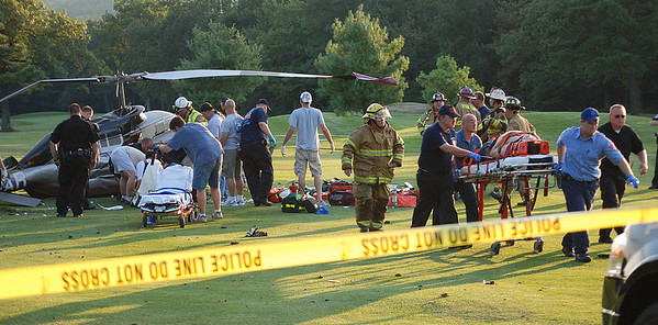Rescuers remove one of the victims of Friday's helicopter crash at Mountain Valley Golf Course.