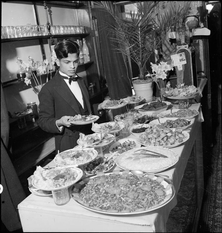 "Miah Jorif, a waiter at the Istanbul restaurant in Soho, at work at the salad table, which, according to the original caption, is ""the pride and joy"" of his heart. Miah is originally from Bengal and has been in Britain since 1940."