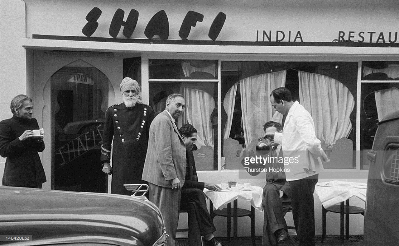A Sikh doorman (left) outside the Shafi Indian restaurant in Gerard Street, London, 17th October 1955.
