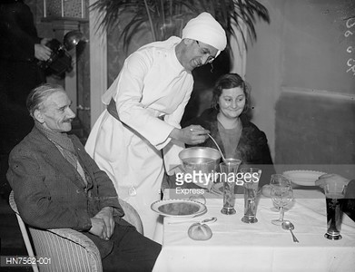 Two unemployed people are served a meal at an Indian restaurant in Regent Street, London.