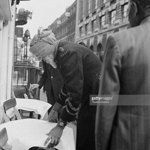 A Sikh doorman outside the Shafi Indian restaurant in Gerard Street, London, 17th October 1955.