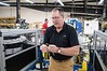 David LaChance — Bennington Banner<br /> Scott Elithorpe, president of Abacus Automation, shows what the machine behind him was built to do — insert plastic clips on dispenser pumps.