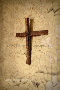 Homemade cross found in a religious building in ruins. Made from rusted building materials that are falling off the building itself.