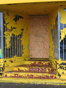 Yellow peeling paint all over the storefront entranceway of a derelict house on Gladstone Avenue in Ottawa, Ontario. © Rob Huntley