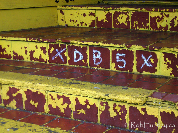 Storefront steps with yellow peeling paint on a derelict house on Gladstone Avenue in Ottawa, Ontario. © Rob Huntley