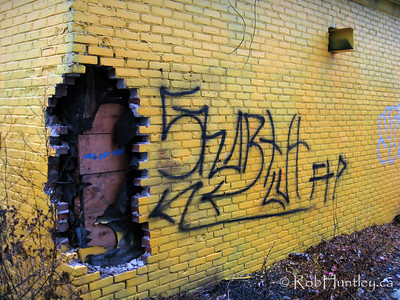 Graffiti leads the eye to the hole in the wall. The brick layer and tar paper has been ripped out of the corner of this brightly painted house. © Rob Huntley