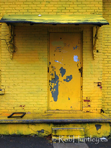 Grungy side entrance of a derelict store and house.