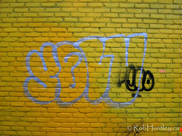 Graffiti on a yellow painted brick wall.