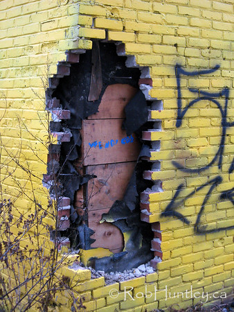 Hole in the Wall. The brick layer and tar paper has been ripped out of the corner of this brightly painted house. © Rob Huntley