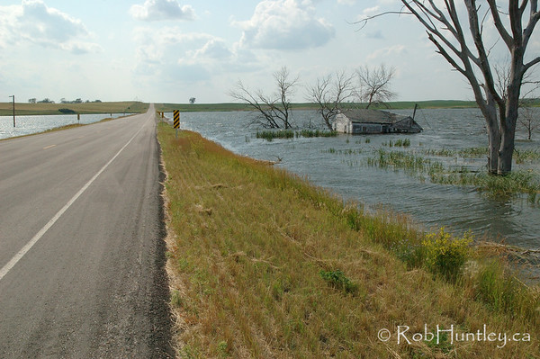 The highway passes straight through the body of water responsible for swamping this derelict on Hwy 46, east of Gackle, North Dakota.  License this photo on Getty Images  © Rob Huntley