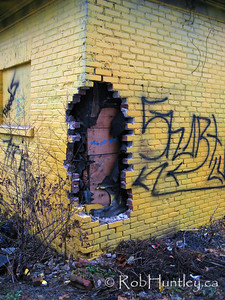 Graffiti on a bright yellow derelict house.