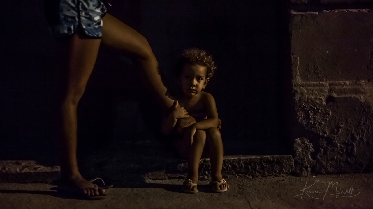 A little girl sits patiently on the streets of Havana while her mother makes a call from a payphone.