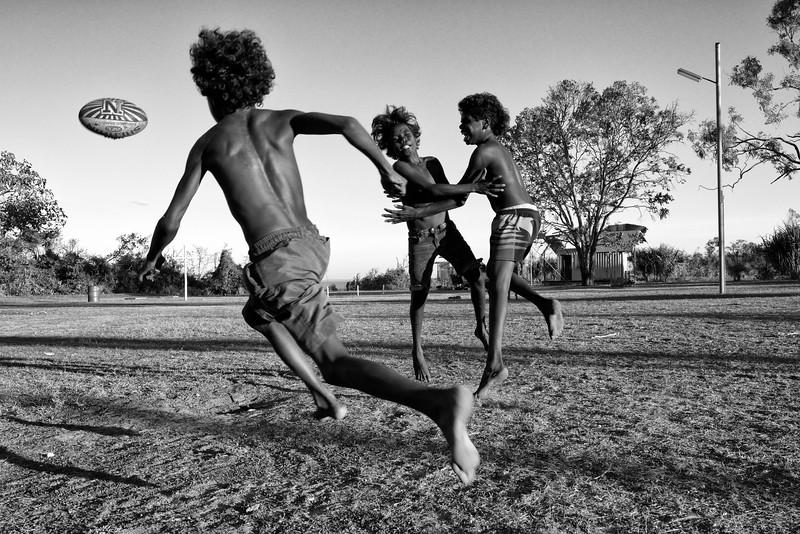 Enfants de Raymangirr, dans la baie d'Arnhem, faisant un match de footy (football australien). Terre d'Arnhem/Territoire du Nord/Australie