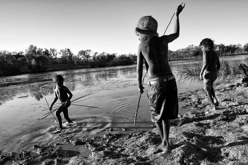 Enfants de la communauté de Ngukurr s'exerçant à pêcher à la lance dans les eaux du Yellow Water Billabong. Terre d'Arnhem/Territoire du Nord/Australie