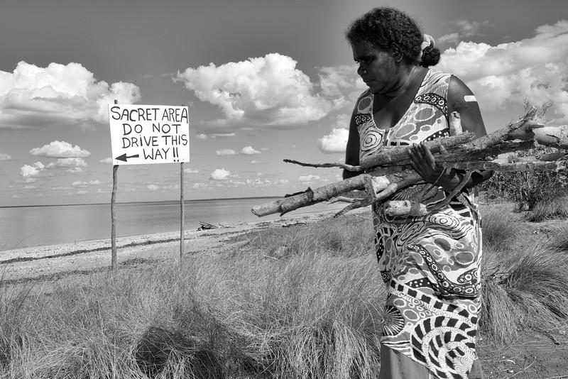 Rina Guyula ramassant du bois mort pour faire un feu sur la plage de Raymangirr dans la baie d'Arnhem (lieu sacré, comme indiqué sur le panneau -avec une faute à sacred/t-). Terre d'Arnhem/Territoire du Nord/Australie