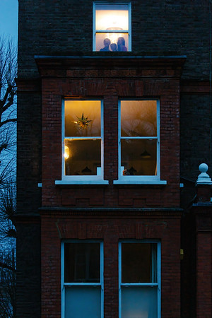 A family look out their window as night falls on boxing day. ©KT Watson   ktwphotographer@gmail.com   www.ktw.photographer   IG: @ktwphotographer