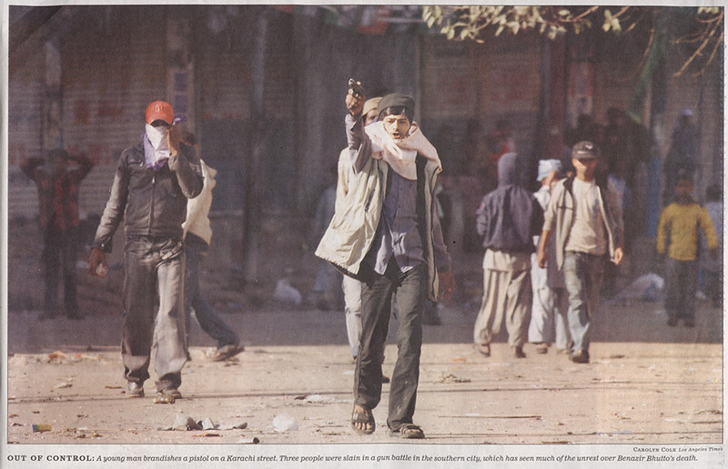"This photo appeared in the Los Angeles Times, 2007/12/30, section A, page 10 in an article about the assassination of Benazir Bhutto.  The photo caption reads, ""<B>Out of Control</B>: A young man brandishes a pistol on a Karachi street. ...""  However, there is something fishy about this photo.  See next entry."
