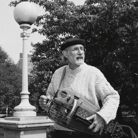 """May 11, 2010. Donald Heller, hurdy gurdy man, Boston Public Garden. This was my first encounter with a hurdy gurdy, which, as a life-long strings player, I found fascinating. The hand-crank turns a rosined wheel that acts as a """"bow,"""" vibrating either two or four strings. The levers under Mr. Heller's left hand stop the strings - analogous to fingers on the fret board - to make the notes, with a couple of the strings sounding as drones. <br /> <br /> The hurdy gurdy originates from the fiddle - it is also called a wheel fiddle - most likely from Western Europe or the Middle East, and is primarily associated with street musicians."""