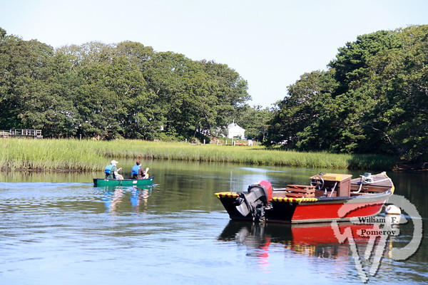 RIVER VIEW Canoeists paddle the Herring River,  past the ever famous red Hero.  Harwich Oracle August 21, 2013 front page