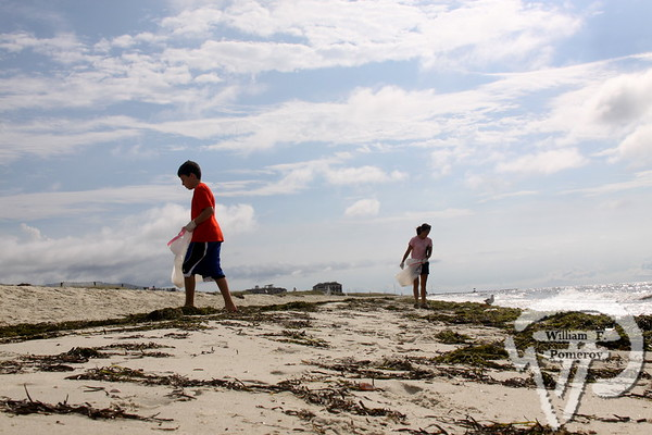 THE COAST IS CLEAN! Coastsweep volunteers Jason Masiello, 12, and his mother Kathy, of Harwich,  search the Bank Street Beach shoreline for trash Saturday.  Harwich Oracle September 19, 2012 front page