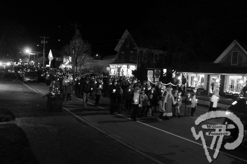"""<font style=""""color: #dab25b; font-size: 14px; font-family: Century Gothic; font-weight: bold; font-style: italic;"""">A candlelit procession strolls down Main Street to the Village Green last Saturday evening to kick off A Seaside Christmas in Orleans. </font>"""