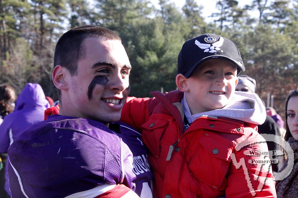 Bourne co-captain Tyler Benotti celebrates a 22-12 victory over Wareham with fan Tom Howie.