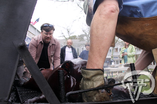 Peter O'Brien assists Seamus Hanrahan  in turning the pig roast.
