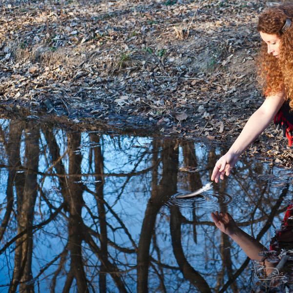 She puts a feather in the pond on a sunny winter day.
