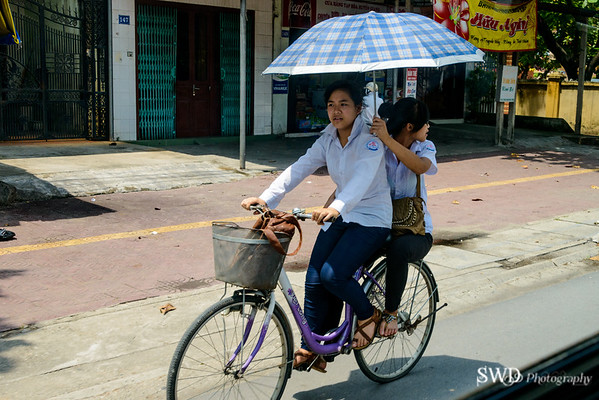 Two girls on bicycle on road to Halong Bay