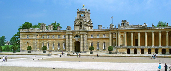 "Blenheim Palace side facade  Blenheim Palace is a large and monumental country house situated in Woodstock, Oxfordshire, England. It is the only non-episcopal country house in England to hold the title ""palace"".  The Palace, one of England's largest houses, was built between 1705 and circa 1724. It was recognised as a UNESCO World Heritage Site in 1987. Its construction was originally intended to be a gift to John Churchill, the 1st Duke of Marlborough from a grateful nation in return for military triumph against the French and Bavarians.   However, it soon became the subject of political infighting, which led to Marlborough's exile, the fall from power of his Duchess, and irreparable damage to the reputation of the architect Sir John Vanbrugh. Designed in the rare, and short-lived, English baroque style, architectural appreciation of the palace is as divided today as it was in the 1720s.  It is unique in its combined usage as a family home, mausoleum and national monument. The palace is also notable as the birthplace and ancestral home of Prime Minister Sir Winston Churchill."