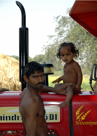 "Father, Daughter, Tractor, 2005. 10"" x 14"". Digital print on archival paper. No doubt the shiniest tractor in Mirzapur District outside of Varanasi, the red, black and chrome machine was a prized commodity for local farmers and a curiosity for their children. The father, stern and protective, kept one hand on his daughter and both eyes on me."