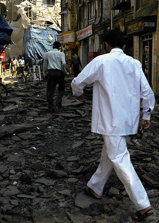 "Stepping Lightly in Bombay, 2005. 10""x14"". Digital print on archival paper. It wasn't a war zone and there were no bombs. Despite being situated in a posh district of Mumbai, there was no remedy in sight for this torn and tattered road. In true Indian fashion, this passage would prove to be no obstacle to daily commerce and only a passing photographer seemed to notice its troubled state."