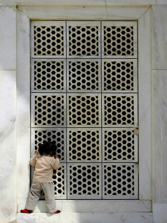 "Peeping Taj, 2005. 10"" x 14"". Digital print on archival paper. The Taj Mahal was pure white in the noonday sun. Birds flanked the grand minarets at each corner of the complex and there was a constant flow of tourists, toting their children and their cameras, working up a sweat trying to capture the perfect shot. This child, with youthful innocence and curiosity, had broken free from the mass of humanity and took a quiet moment to see what lay ahead beyond the gate."