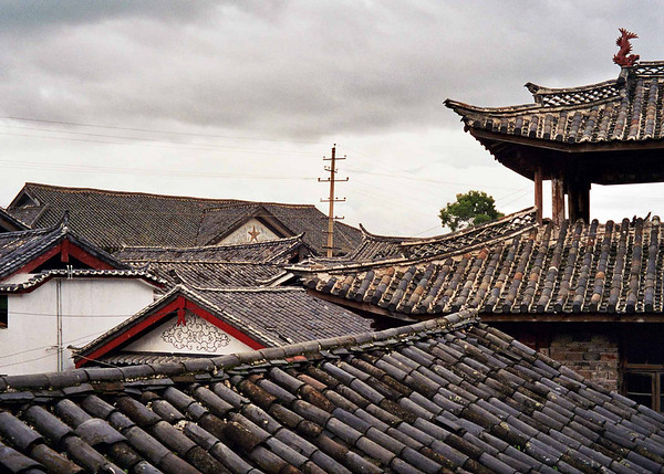 "Lijiang Rooftops, 2002. 10"" x 14"". Digital print on archival paper. The old city of Lijiang is at the same time a maze of alleyways and cigarette stalls as it is a step back in time. The town offers endless opportunities to wander and explore, with traditional guesthouses providing food, shelter and the opportunity to use the neighbourhood latrine. Despite a full-time caretaker, who's room is settled in between the boys on the left and the girls on the right, visits to the latrine required ample smatterings of tiger balm under each nostril."